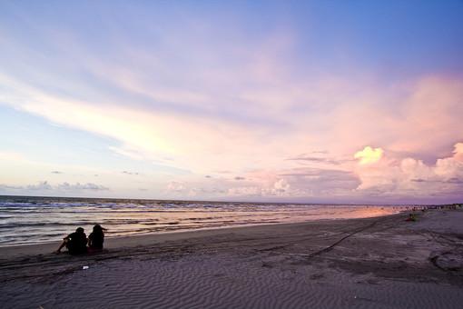 ビーチを眺めるカップルの写真