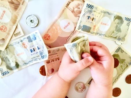 おもちゃのお金と子供の手の写真