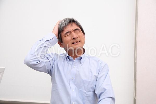 頭を抱えるシニア男性1の写真