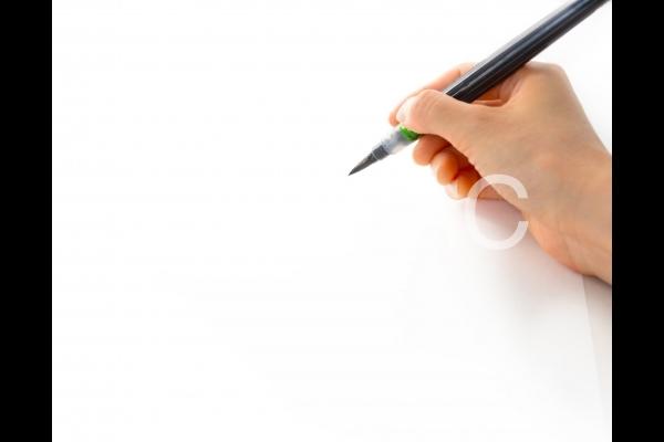 筆ペンで年賀状を書く手の写真