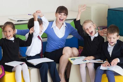 キューブクッションに座る小学生と先生21の写真