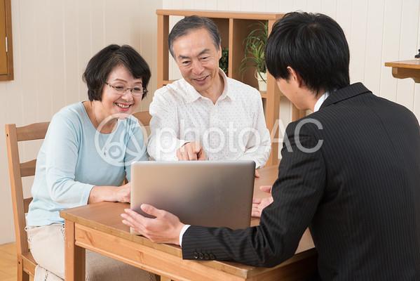 営業マンから説明を受けるシニア夫婦4の写真