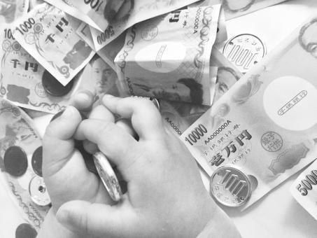 おもちゃのお金と子供の手 (モノクロ)の写真