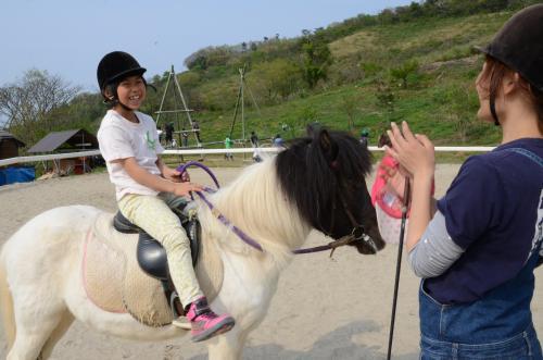 1人で馬に乗り、大学生ボランティアに「すごーい」とほめられた戸板実穂さん=鳥取市越路