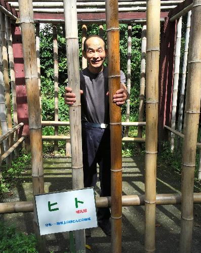 「ヒト」と書かれたおりに入る田中直樹さん。来園者が入り記念撮影できる=東京都の羽村市動物公園
