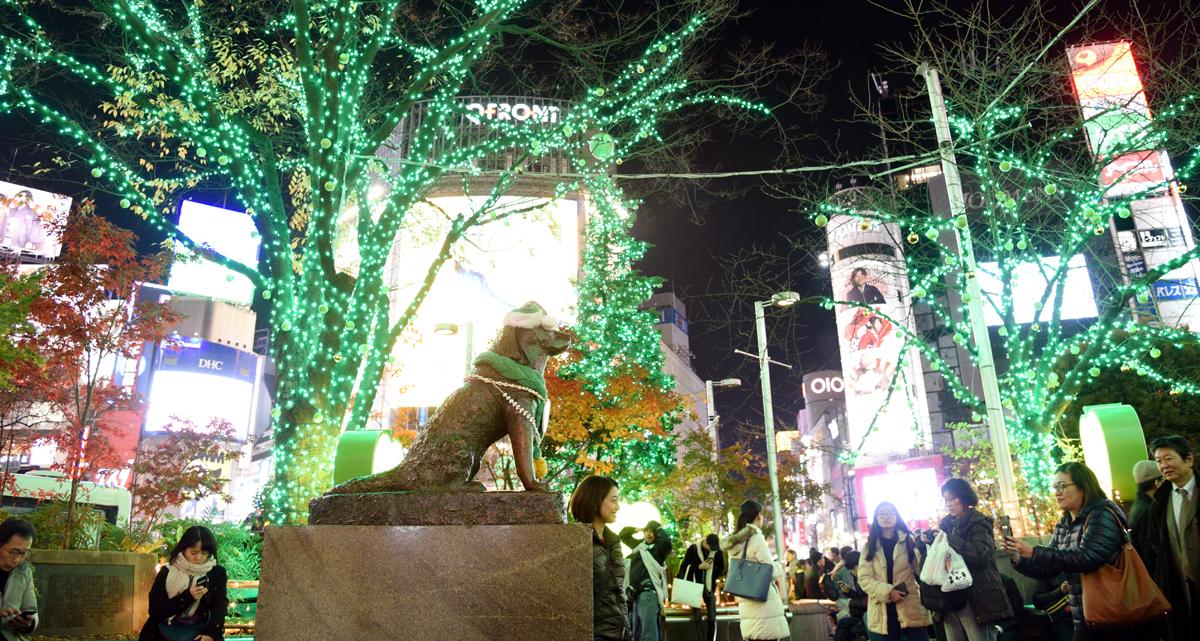 ライトアップされたハチ公前広場で記念写真を収める人たち=東京都渋谷区