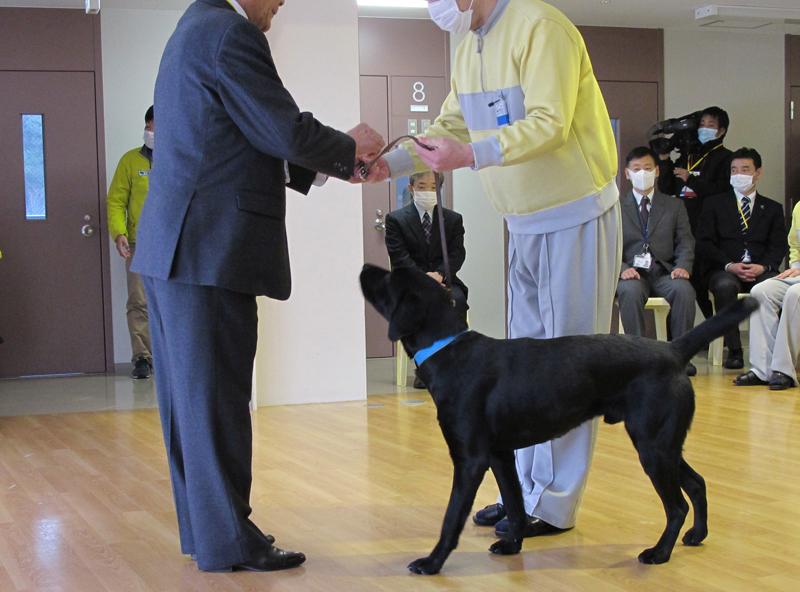 修了式で、日本盲導犬協会の井上幸彦理事長にパピーを引き渡す訓練生(c)大塚敦子