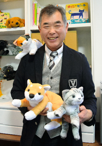 鳴くネコやイヌの商品に囲まれるトレンドマスター・中田敦社長=川崎市