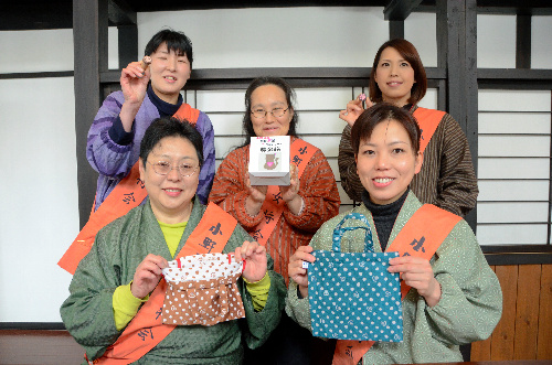 グッズや募金箱を手にする小野川温泉女将会のメンバー