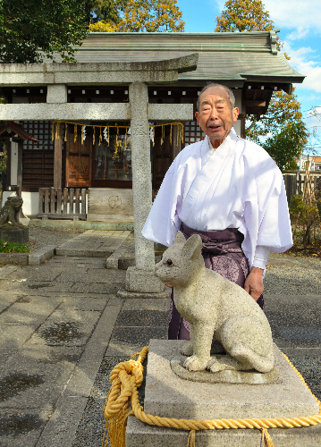 蚕影神社とこま猫の間に立つ宮崎洋さん=東京都立川市砂川町