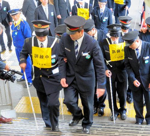 目隠しをして白杖(はくじょう)を持った駅員を誘導しながら階段を上る講習