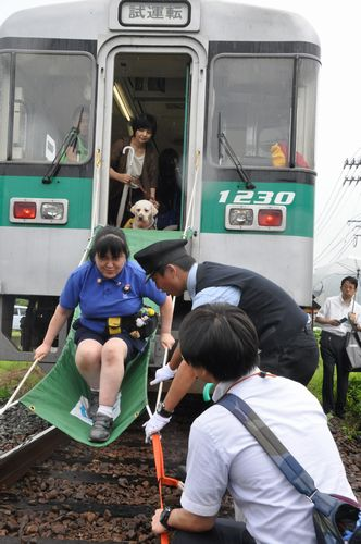 避難シューターを使った訓練をする鶴野さんら=阿南市のJR牟岐線