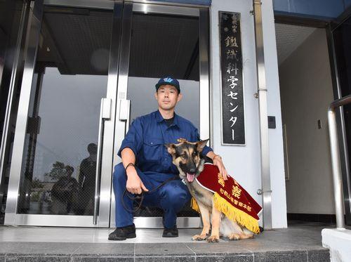 ヨハン号と警察犬係の庵野巡査部長=和歌山市西の鑑識科学センター