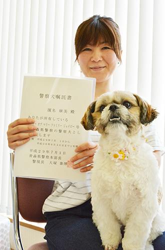警察犬の嘱託書を持つ浜名さんと「まる」=青森県弘前市