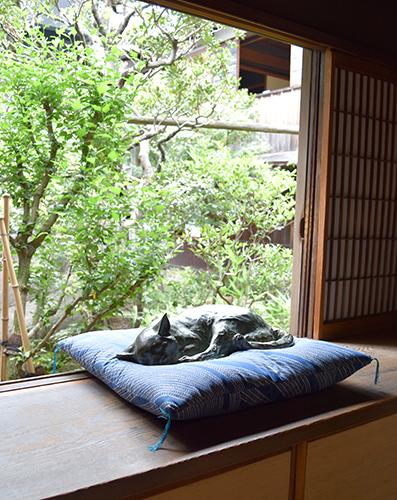座布団で寝ているように展示された猫の彫刻