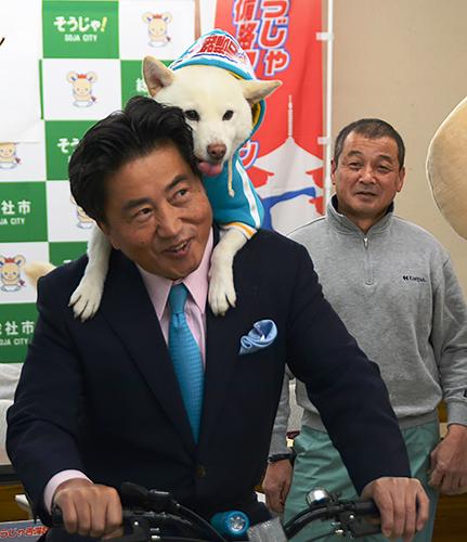 自転車に乗る片岡聡一市長の背に乗る太郎と、飼い主の松本光正さん(右)=岡山県総社市役所