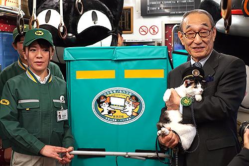 和歌山電鉄の小嶋光信社長(右)に抱えられ、集配コンテナの前で記念撮影する伊太祈曽駅長の三毛猫「よんたま」=和歌山市伊太祈曽