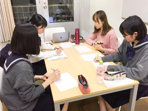徳久さん(右奥)と生徒たちがグループディスカッションを練習するようす
