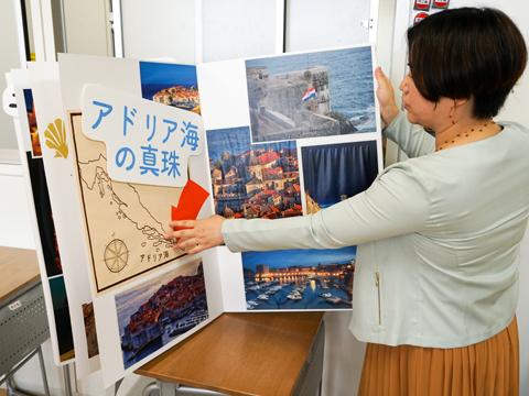 生徒がプレゼンで使用した作品を解説する近藤先生。