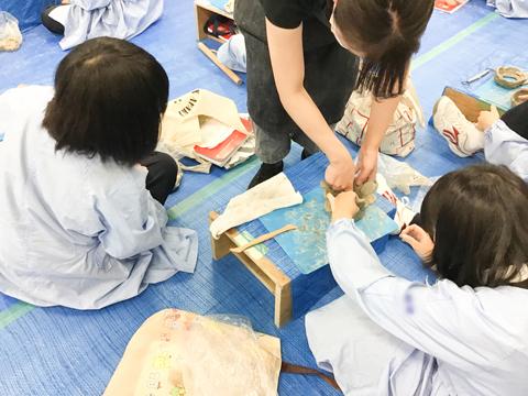 陶芸専門の先生からアドバイスをもらう生徒たち