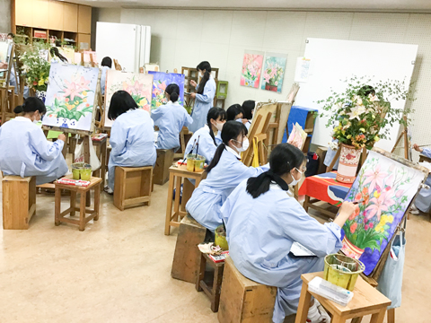 花瓶に生けられた花を真剣に見つめ、描画に集中する生徒たち