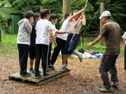 板を使った第2の課題は、ロープを使ってもう1枚の板に全員が渡りきること。なかなか渡りきれず振り出しに戻る中、包容力を発揮した1人の生徒が。その場で「母性」というあだ名がつき一体感を生み出していました。