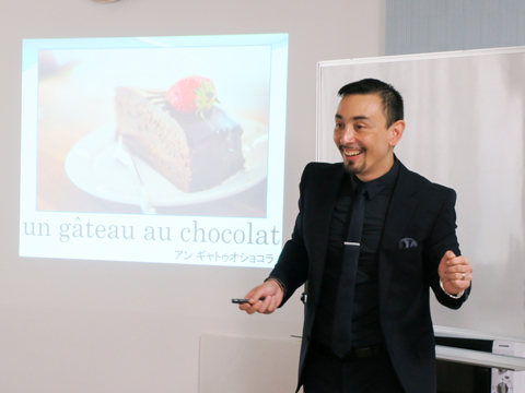 スライドの画像を交えてガトーショコラやマカロン、カフェオレなどの発音を教えるカルトン先生。