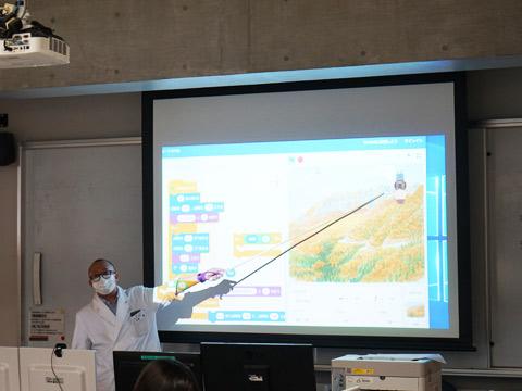 「プログラミング教室」で指導者からプログラムの見本を示すようす