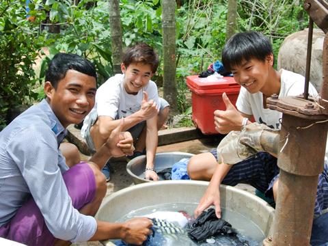 井戸水を使って洗濯する中垣くん(中央)。ホームステイ先の家族が手伝いに来てくれました。