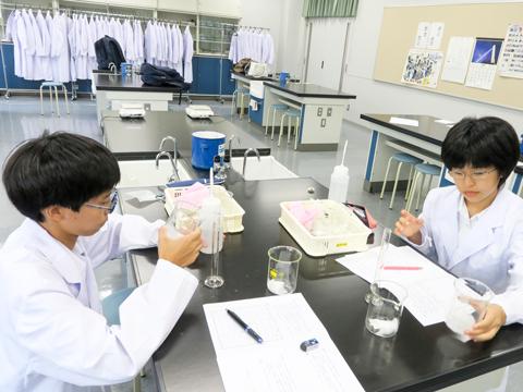 紙おむつの中身と脱脂綿に水を加えていく、中2の阿部くん(左)中1の岸田さん(右)