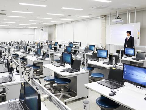 80台以上のパソコンが並ぶコンピューター教室。机の中央には教員のパソコン画面を映し出すモニターがあり、生徒はスムーズに作業できます