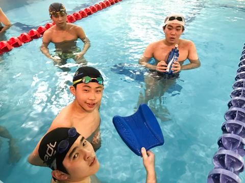 練習の合間にひと息入れるAくん(写真中央)と競技水泳部の皆さん。毎日切磋琢磨しながら練習に励んでいます。