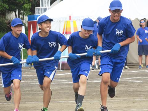 中学生が学年対抗で挑むのは、タイフーンと呼ばれるひと癖ある競技。ひとつの棒を4人で横並びに持ち、コーンの置かれた場所で一回転しながらコースを走り抜けました。