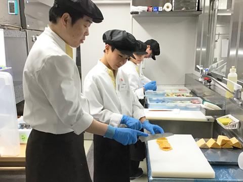 ホテルの方に指導を受け、料理の盛り付けを行う鈴木くん。