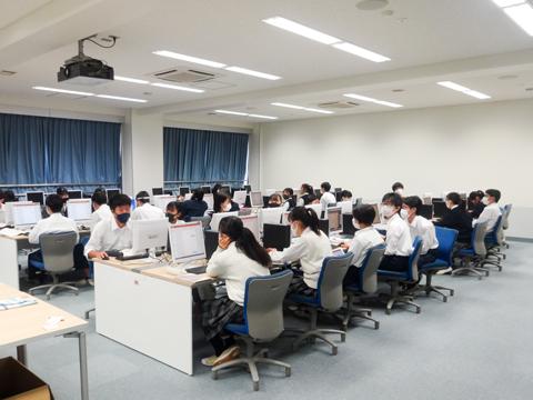 コンピューター・ガーデン 最新の設備を使い、中学校の技術の授業では情報モラルやタイピング、プログラミングを学び、高校の情報の授業ではプログラミングやネットワーク学習を行っています。「前面には先生のパソコン画面を写す大きなモニターがあります」