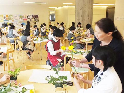 池坊の大嶋晴月先生から生け花を教わるようす