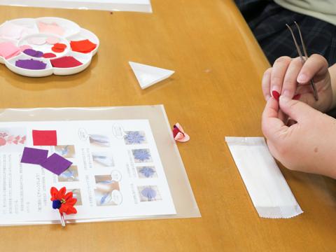 家庭科の授業では、江戸時代から伝わる工芸品のつまみ細工を手作り体験。着物の生地の切れ端などを組み合わせて小さなお花を作るもの。浴衣を着るときの髪飾りによいと生徒に人気の手芸です。