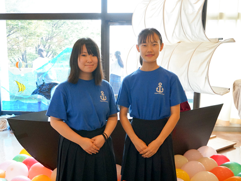 委員長のA.Oさん(左)と副委員長のA.Sさん(右)。後ろの船は、「出航」という今年度のテーマに合わせて実行委員が制作したシンボル。