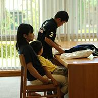 [図書室]一緒に椅子に座って本を見る親子