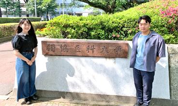 大学の校門の前に立つ増田さんと井上くん