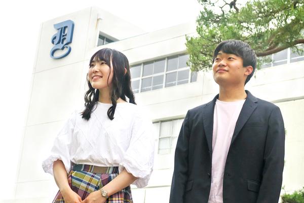 校舎の前に立つ増田さんと井上くん