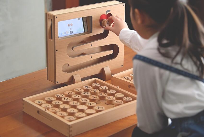 テイ・デイ・エス、木製ひらがなブロックとスマートフォンが連動した知育玩具「ころぴゅーた」のクラウドファウンディングを開始