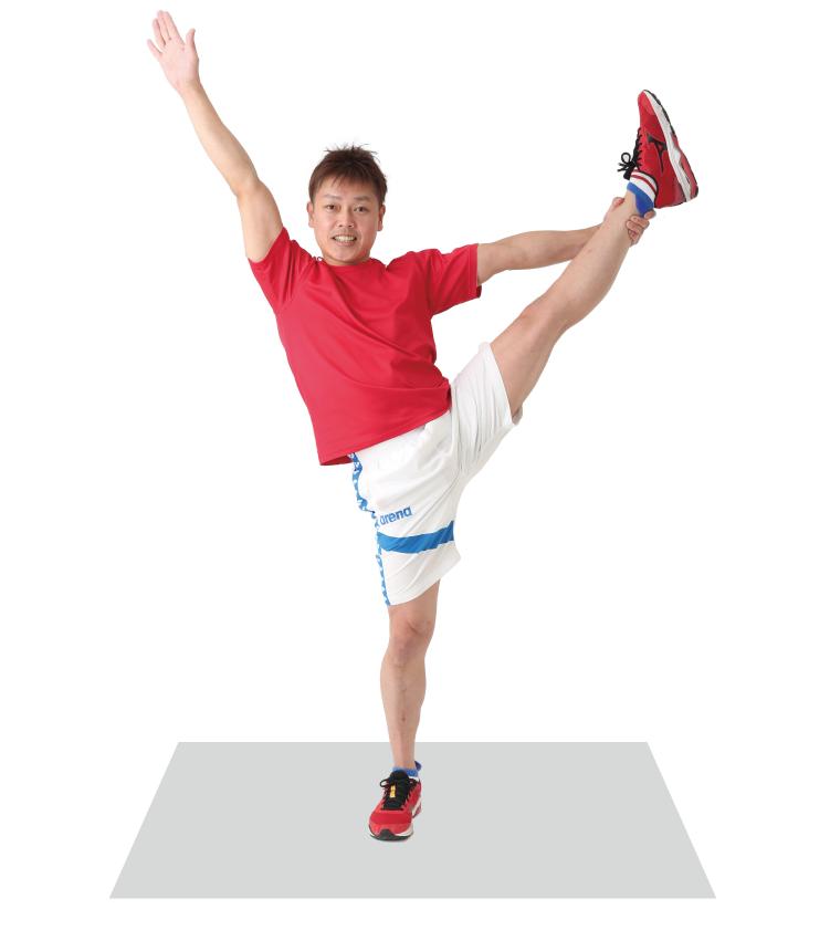 右手をまっすぐ伸ばし、左足を上げて左手で足首を持ちバランスを取る