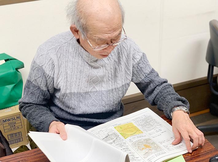 八幡町のまちづくり計画を広げながら話す北田一浩さん
