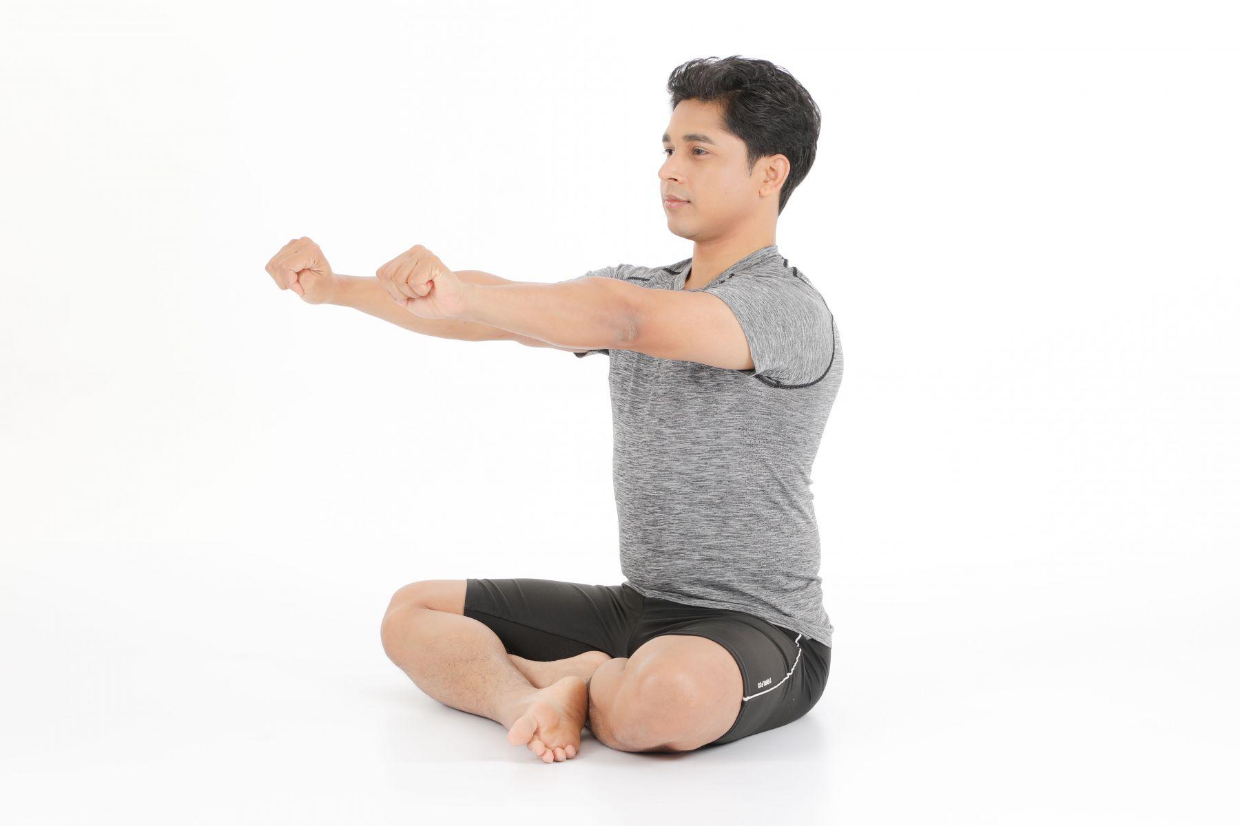 吸氣,雙手伸直抬高至肩膀高度。雙手握拳。