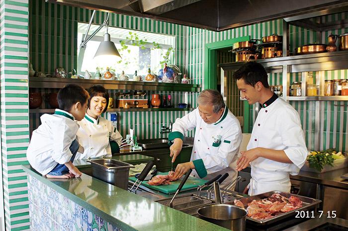 何氏父女熱衷於下廚, 圖為2011年家庭旅行 至義大利,何壽川(右 二)與何奕佳(左二) 參加當地廚藝教室,小 孫子好奇爬上料理台, 觀察爺爺解剖兔肉。