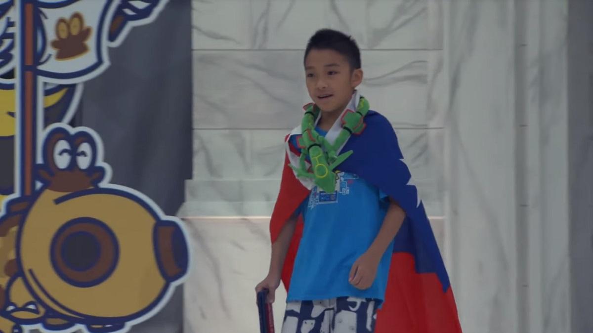 年僅10歲的台灣選手吳比,披國旗走上舞台。圖/ The Official Pokémon YouTube channel影片截圖