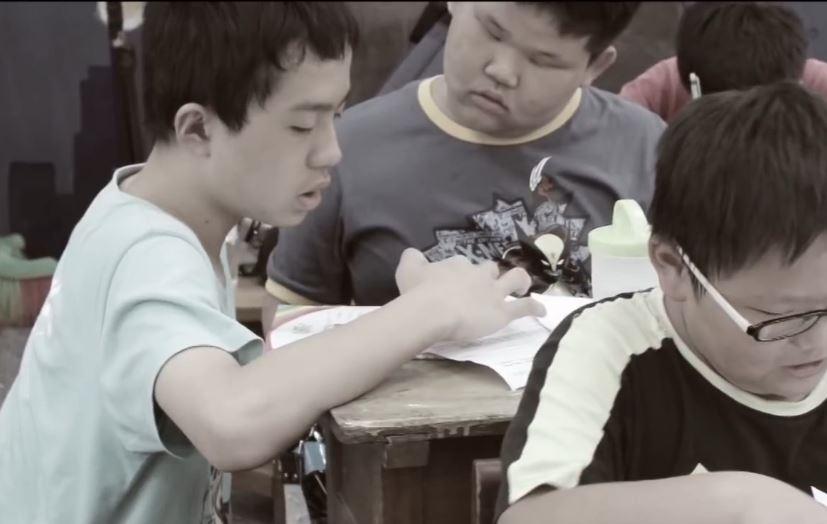 ▲凱威仔細地指導孩子課業,儘管說話速度偏慢,但也因為這樣孩子都能跟得上教學內容。(圖片提供/桃園市愛鄰舍協會)