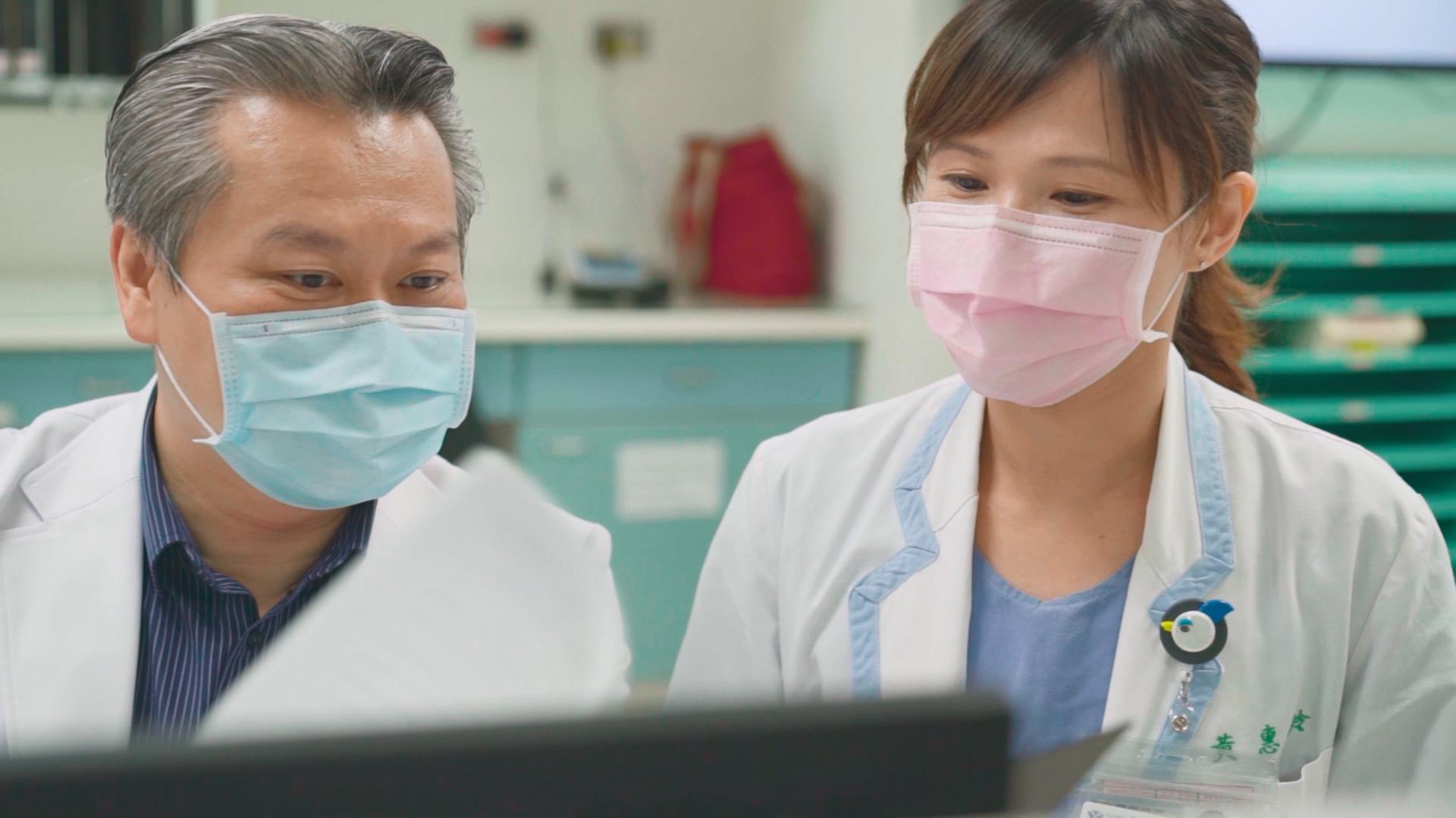 陳志金醫師與專科護理師黃惠鈴正在討論病例