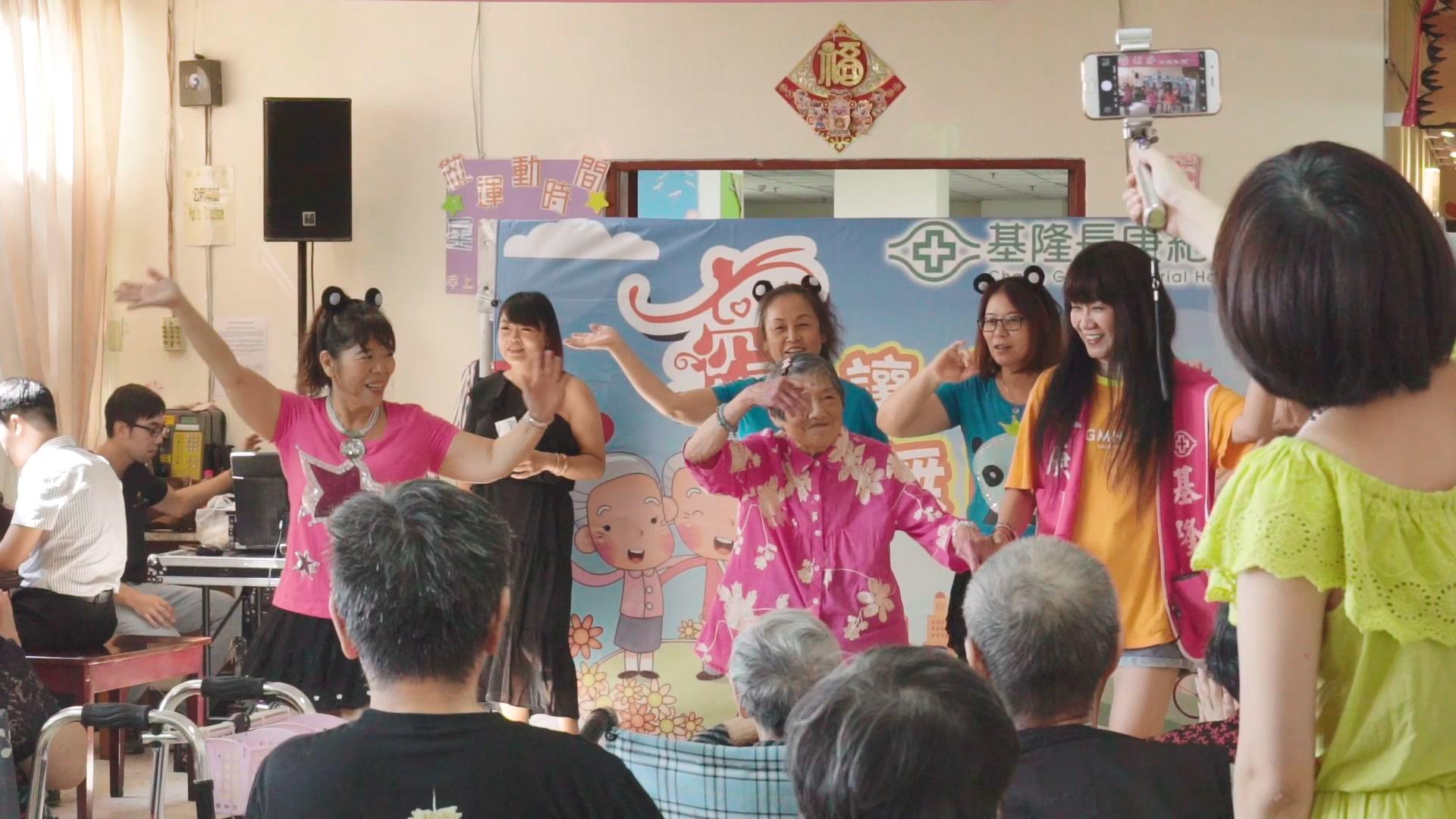 基隆恆安舞台上身著桃紅色花上衣的李足奶奶活力十足,與志工團體載歌載舞